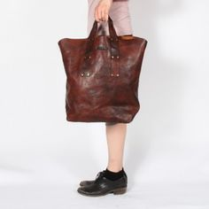 Larger tote, taller shape Very short handles that are attached with rivets, simple paneling with pinched corners