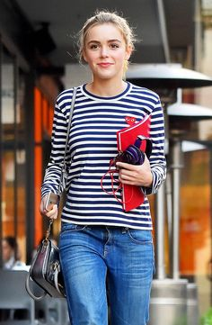Kiernan Shipka in a Commes Des Garçons Play striped t-shirt, blue jeans, and a silver bag