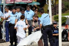 インド洋の仏領レユニオン島(Reunion Island)で、新婚旅行中にサメに襲われ死亡した仏人男性の妻と話す警察官ら(2013年5月8日撮影)。(c)AFP/RICHARD BOUHET ▼9May2013AFP|新婚旅行中の男性がサメに襲われ死亡、仏領レユニオン島 http://www.afpbb.com/articles/-/2943017