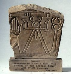 """Tapering limestone stele fragment, detail of a Tanit symbol flanked by a hand and a caduceus. At the ends of crossbar are two curved """"arms"""". There is a curved headdress possibly a crescent moon below the circle. Unusual features - use of caduceus finial with snakes' heads; elongated lozenge may be either male or female genitalia."""