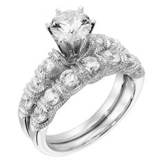 Been searching for a trendy version of your great grandmother's gorgeous solitaire engagement ring? Look no further! At a low price, heirloom luxury is yours with this Round Brilliant cut centerpiece, highlighted by accent jewels and draped with decorative millgraine detailing. Center stone pictured: 1.03 carat Round cut (2.04 Round cut on hand.) Center stone available in a range of sizes. See menu above. Six prong-set Round Brilliant cut accents Order additional services like a personal ...
