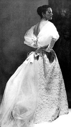 Balenciaga's beautiful gown of ivory embroidered lace with tulle train held up by satin bows, 1954