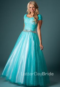 This full ball gown is done in a soft sparkle tulle. The wrap waist is accented with a beaded band and sweetheart neckline. A classic and flattering modest prom dress.