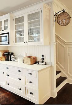 White kitchen cabinets, glass fronts, bead board and cup pulls