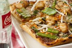 Thai Chicken Pizza.  Thai peanut sauce, chicken, shredded carrots, snow peas, roasted peanuts, bean sprouts & cilantro.  AWESOME!!!