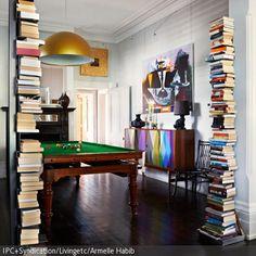 Zwei Bücherstapel, die sich als Bücherregale erweisen, säumen den Eingang zum Billiardzimmer. Das bunte Sideboard zusammen mit dem abstrakten Wandbild und den …