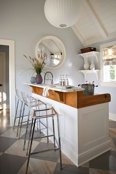 good use of small space.  bar in a poolhouse?  love the mix of materials, the light fixtures, floating shelves...