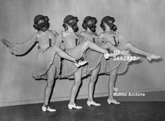 Gas Mask Girls: Dancers at the Windmill Theatre in London, practice a routine wearing gas masks and hard-hats with their costumes. Jan 1940