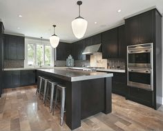 Dark cabinets, grey countertops and light wood floors.like the floor color with dark cabinets. Would go with lighter countertop though. Dark Wood Kitchens, Black Kitchens, Luxury Kitchens, Home Kitchens, Grey Countertops, Kitchen Countertops, Kitchen Flooring, Kitchen Backsplash, Backsplash Ideas