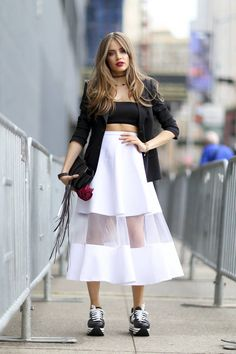 Lookée en baskets compensée noire avec une jupe taille haute blanche et transparente. Bandeau noir et veste noire