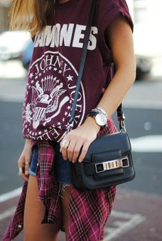 with short shorts, plaid layer, and structured bag.