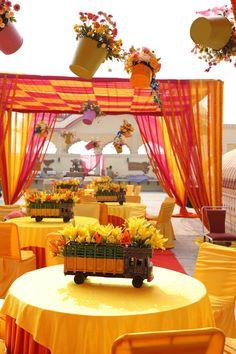 Unique hanging flower pots with mini trucks as table centerpieces in Mehendi decor  WedMeGood  #wedmegood #indianweddings #decor #floraldecor #flowers #yellowlily #tabledecor #centerpieces #tablecenterpieces #decor #mehendidecor