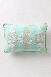 Antropologie pillow- bright colored fabric with antique doily tacked on top.  Coordinating piping.