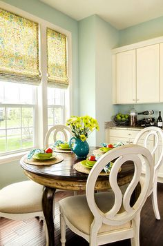 pale seafoam green walls, kitchen, cream cabinets, cream dining chairs, wood floors (Sherwin Williams, Crystal Clear)