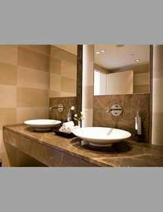 The unique simple spigots hover over the modern bowl basins, and are encapsulated in fine gray stonework. Separate dispensers can also be seen, while a shared bowl of rolled hand towels unite the area. Bathroom Vanity Units, Double Sink Bathroom, Double Sink Vanity, Master Bathroom, Grout Repair, Italy House, Granite Stone, Home Decor, Bathrooms