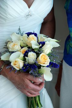 The indigo hue of these blue wedding flowers mesh gorgeously with the cream colored roses and stark white callas. http://thealternativebride.com