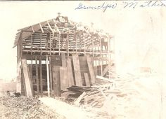Photo of Clarence Delos Mathie helping to build a barn. Date unknown.
