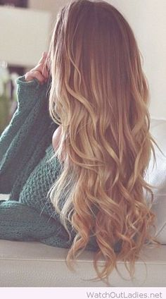 Very long blond curly hair and a green sweater