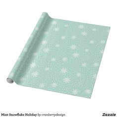 Snow flakes of all sizes decorate this Christmas wrapping paper in a fun pattern that gives winter holiday charm to any gift.