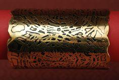 Szeroka, efektowna bransoleta w kolorze złotym.