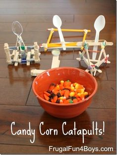 Candy Corn Catapults - hands on math and science learning fun (STEM). Supplies needed: spoons, popsicle sticks, pencils, elastics, clothespins, bottle caps.