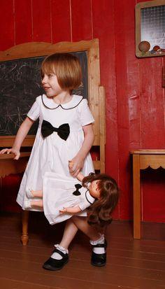 La robe Clothilde blanche avec son petit nœud noir, idéale pour les cérémonies !