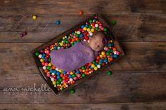 newborn girl in crate with gumballs on wood floor