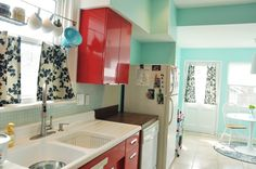Black & white curtains in aqua and red kitchen