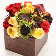 "Elegance and sophistication come to mind when we admire this tightly clustered arrangement of contrasting rich and creamy tones. Arrangement measures 7""x7""x10"" and includes Crème de la Crème roses, Red France roses, sunflower pods, Stelle roses, dahlias, Hypericum berries, red Safari Sunset, dried pomegranate, and echinacea"