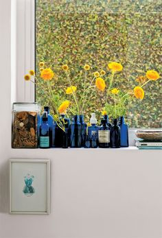 Os arranjos de Rebeca são poesia nascida da simplicidade é o caso dos ranúnculos na janela do lavabo: o azul dos vidros de loção usados valoriza o amarelo da flor.