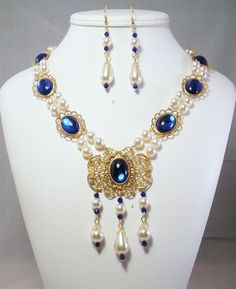 This hand-crafted, professionally made jeweled necklace was created based on the jewelry worn by royalty and the landed gentry of the Medieval and Renaissance Eras. It will add that finishing touch to any noblewomans attire.     Made From:  18 by 13 mm and 25 by 18 Acrylic Cabochons set in individual gold tone brass settings  Gold tone brass filigree  Czech Glass Off-White/cream Pearls and drops  Swarovski Bicone Beads  Gold Plated Findings  @17 inches plus a 3 inch extender  I love…