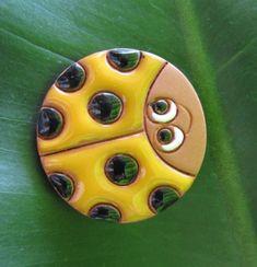 broche de cerámica esmaltada.mariquita amarilla barro.,esmaltes 980°c.,broche metal plateado artesanal,cuerda seca.