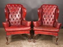 pair of chippendale style mahogany wing chairs covered in leather with tufted backs scroll out