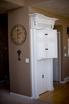 Trimwork around kitchen pantry to look a built-in armoire. Such a smart and easy transformation!