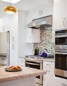 Stainless steel appliances, white slab door custom cabinets, UBC sagebrush custom backsplash, and marble countertops.