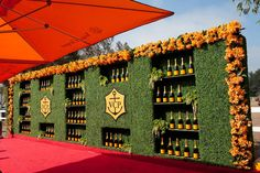 The press wall was made up of 36 feet of faux hedging with recessed bottle shelves, a pair of logos, and a 56-foot-long border of silk flowers.