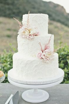Simple wedding cake with pale flowers.