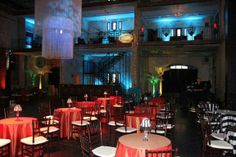 Black & white stripe and red table linens, chivari chairs and small table lamps for a Cuban Street Themed Corporate Party at Jeune Lune at Aria in downtown Minneapolis