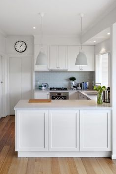 white kitchen + wood flooring + pale blue subway splashback