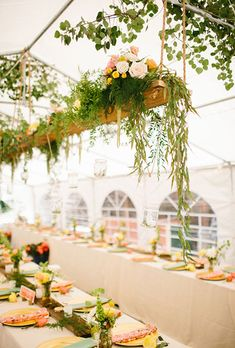 Brides.com: . April's Gardens created beautiful swing-inspired floral chandeliers to hang inside this tented reception space.