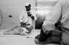 "Two men remove the excess fat from the ham and prepare it for the next phase called ""disossatura."" Photo by: Alessandro Iovino 