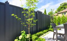 Vertical palisade fence with moldings | Vertical palisade fence with moldings we built for Mrs. Lo Papa in Ville Mont-Royal. This red cedar fence has been stained black to contrast with the pale pavers and the greenery.