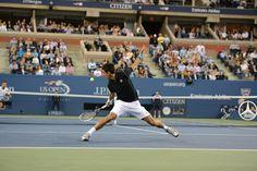 Top seed Novak Djokovic slides for a backhand during his quarterfinal match. - Rob Loud/usopen.org