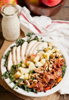 This healthy kale salad is loaded with chicken, bacon, apples, and walnuts.