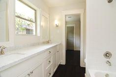 Jack & Jill bath features Carrara marble & white subway tile.  Dual sinks & tub/shower combo.