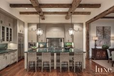 As the heart of the home, the kitchen opens to the breakfast area and family room. Custom cabinetry by JP Inside Trim & Cabinets balances the granite countertops from Walker Zanger. Barstools by The Wicker Works, purchased at Culp Associates, provide seating, while lanterns with custom chains, refurbished by Peck & Company, hang from rough-hewn beams.