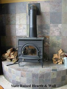custom slate design raised hearth for wood stove bench provided by the sandel group