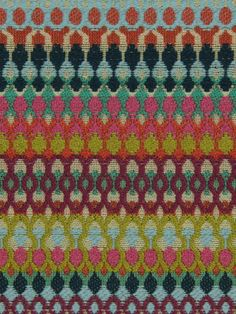 Modern upholstery fabric in a geometric design of teal, fuchsia, orange, pistachio green, indigo, aqua, ivory and pomegranate red.
