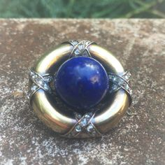 #Russian #gold #brooch with a large #lapis lazuli and #old-cut #diamonds.  Brooch made of gold, 56 zolotniki purity, there is a maker's mark AA, but I couldn't identify an exact jeweler.  Ca. 1900 Diameter of brooch is  2.6 cm, weight - 13.2 gr. In the center there is a large round  lapis lazuli (diameter 12.8 mm) that has deep blue color  with gold stripes.