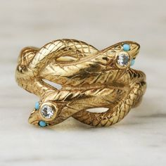 An art deco 14k gold entwined snake ring with diamonds and turquoise